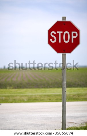 A stop sign in a rural town in front of a farm