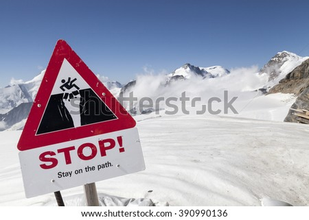 A 'Stop' sign on a snow capped mountain in Switzerland against a blue sky - stock photo