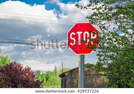 A stop traffic sign behind a tree.