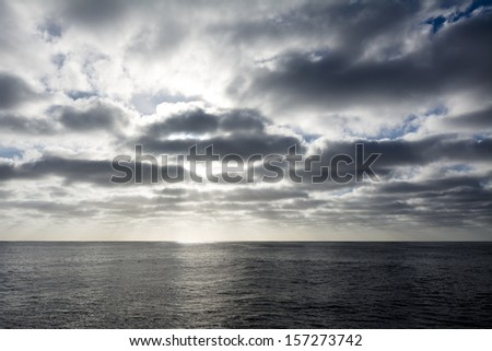 A stormy sky over the ocean as the sun is setting. - stock photo