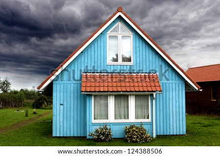 A stormy sky surrounds a small and peaceful blue wooden house - stock photo