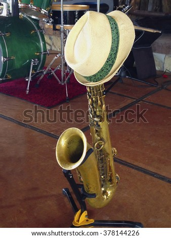 A straw hat resting on a saxophone on stage - stock photo