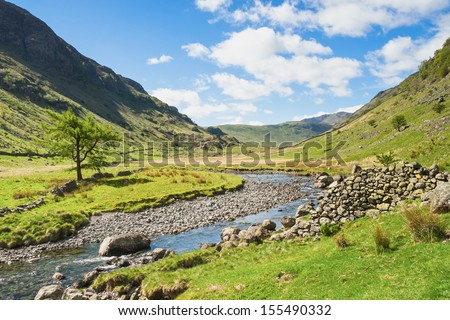 A stream running through a mountain valley in the English Lake District. - stock photo
