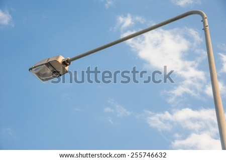 a street light pole with a blue sky background. - stock photo