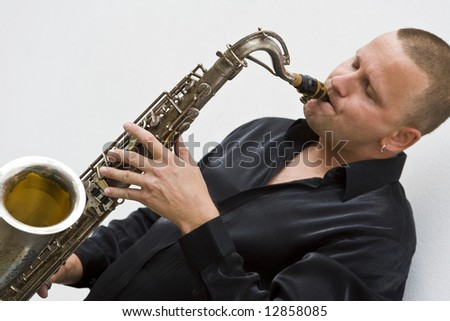 A street musician leaning against a white wall and playing his saxophone. - stock photo
