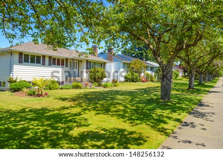 A street of family houses in suburban area of Vancouver, Canada with pedestrian pathway and tree alley in front - stock photo