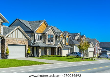 A street of family houses in suburban area of Vancouver with concrete side walk and asphalt road in front. Residential houses with cars parked on driveways in front. - stock photo