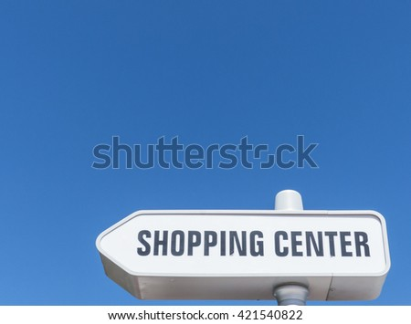 A street signpost with the capture shopping center against blue sky.