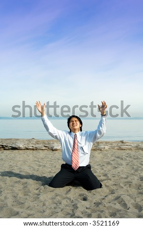 A stressed businessman crying and kneeling on the beach