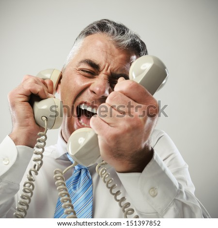 A stressed businessman yells loudly into the three handsets that he is holding. - stock photo