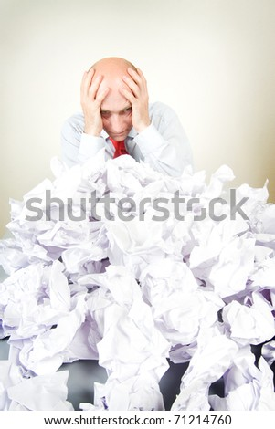 A stressed man holding his head behind a pile of papers. - stock photo