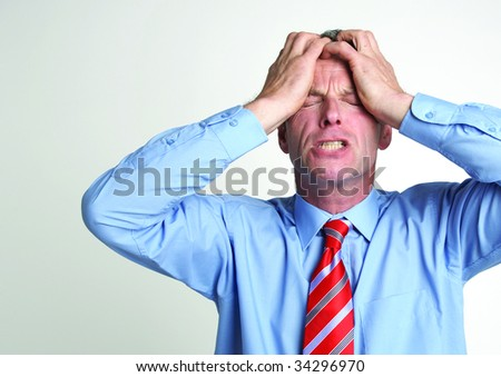 A stressed out businessman holds his head in hands - stock photo