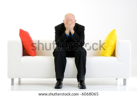 A stressed out businessman in a suit holds his head in his hands. Sadness, depression, worry, or a headache.