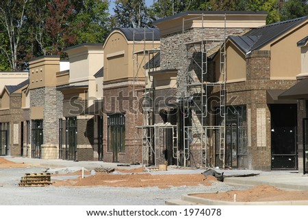 A strip mall under construction, designed to appear like a small town main street. - stock photo