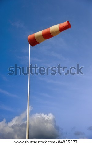 A striped weather vane at the airfield against blue sky - stock photo
