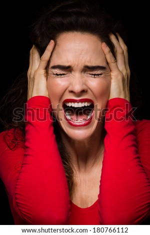 A strong dark image of a very upset, angry and emotional woman, screaming. - stock photo