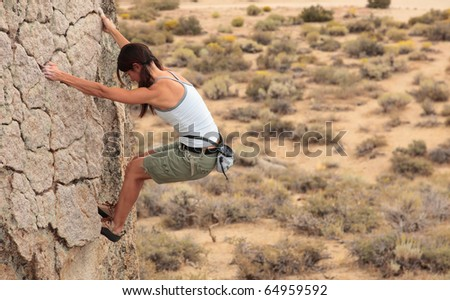 A strong female climber ascends a rock face near Bishop California.
