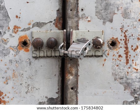 A strong lock on an old rusty metal door