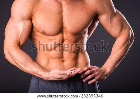 A strong man, bodybuilder, posing on a gray background. A man holding a pill, amino acids, dietary supplements. He looks at them. Sports, bodybuilding, special sports nutrition. - stock photo