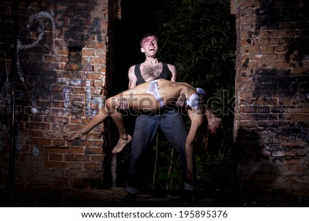 A strong man holding a bloody girl - stock photo
