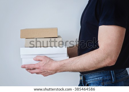 A strong man in jeans and black t-shirt is holding three boxes in his hands.   - stock photo