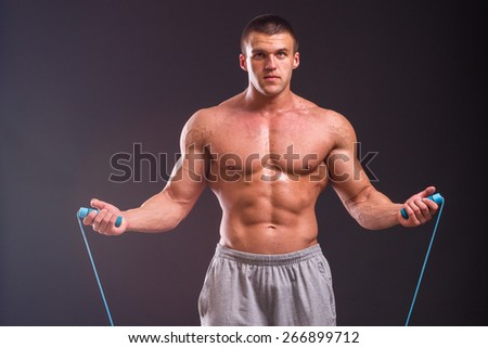 A strong man with a rope. Muscular bodybuilder posing on a black background, shows his muscles. - stock photo