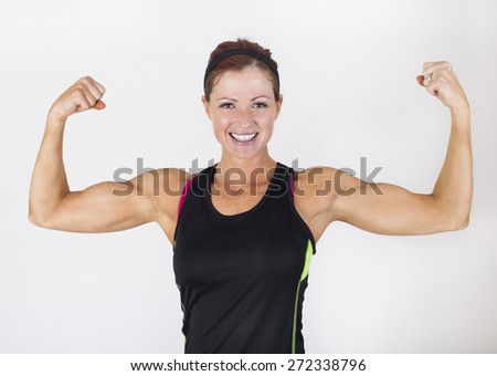 A strong muscular woman flexing her muscles.  Beautiful woman Isolated on a white background - stock photo
