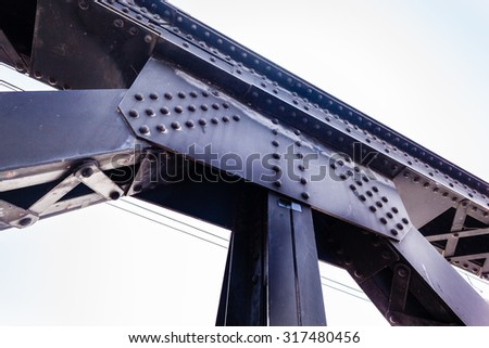 a strong riveted steel beams structure of a railway bridge - stock photo