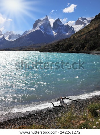 A strong wind blows turquoise waves on the lake, grand cliffs of Los Kuernos covered with snow and ice.  Magic beauty of Lake Pehoe - stock photo