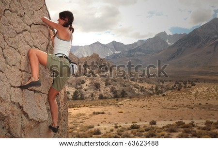A strong woman climbs up a rock face.