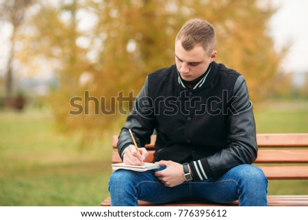 A student in a black jacket sits in a park on a bench writes down his thoughts in a notebook. Handsome boy