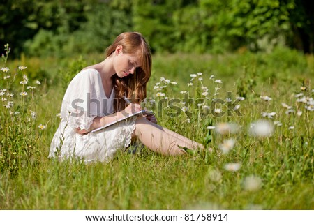 A student takes notes on a summer meadow - stock photo