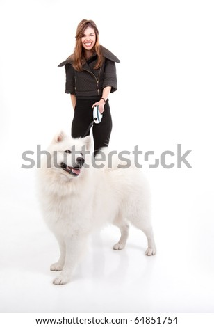 a studio image of a young woman, dressed in black, smiling, walking her white dog. the dog is in front of her, posing from a side and looking to the other side. - stock photo