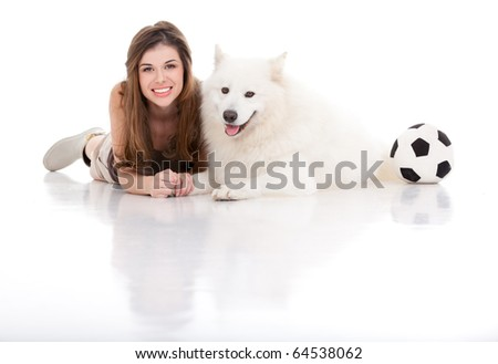 a studio image of a young woman with a white dog, both posing by sitting  their belly, holding hands, smiling, with a football on their side. - stock photo