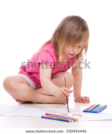 a studio portrait of a nice little girl drawing with paint and brush isolated on white background