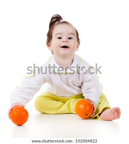 a studio portrait of a smiling little girl with oranges isolated on white background - stock photo