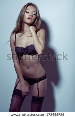 A studio shot of a beautiful and sexy girl with long hair wearing  lingerie - stock photo