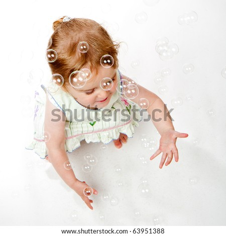 A studio shot of a two year old girl trying to catch soap bubbles.