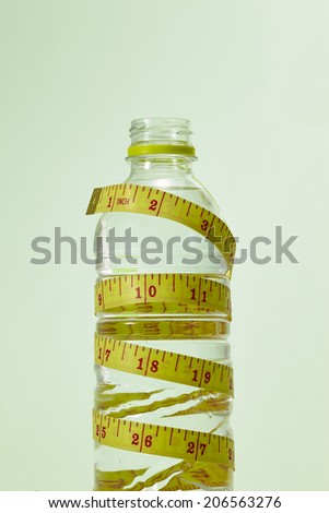 A studio shot of a yellow tape measure and a water bottle isolated on green background - stock photo