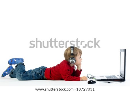 A studio view of a young preschool boy, laying on the floor and listening to music or a video on a laptop computer.