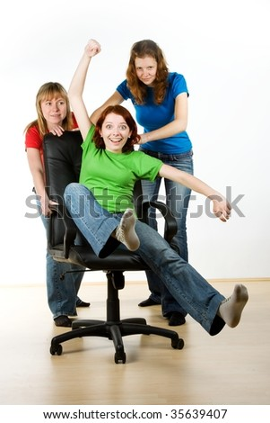 A studio view of three women playfully rolling around on an office chair.