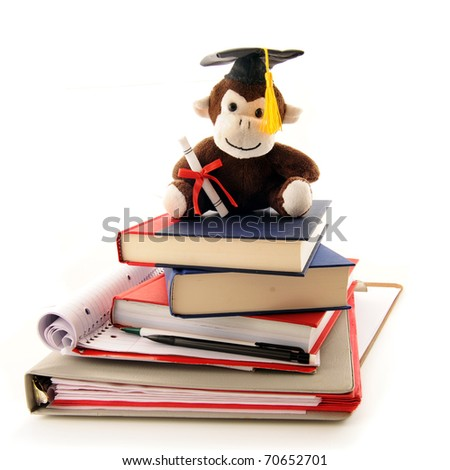 A stuffed monkey with a graduation cap and diploma sitting on top of a pile of used notebooks and texts.  Isolated on white.