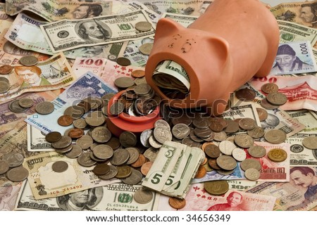 A stuffed Piggy Bank on top of a pile of mixed Foreign money including US, Taiwan, Indian, Hong Kong, Honduran, Malaysian and Korean currency - stock photo