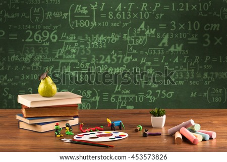 A stuffed school desk with green blackboard in the background full of numbers, calculation - stock photo