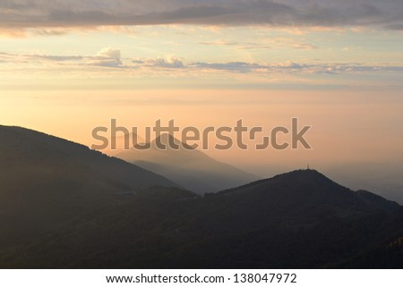 A stunning sunrise in backlight with mountain silhouette and dramatic sky. Location: western Alps, Torino Province, Italy. - stock photo
