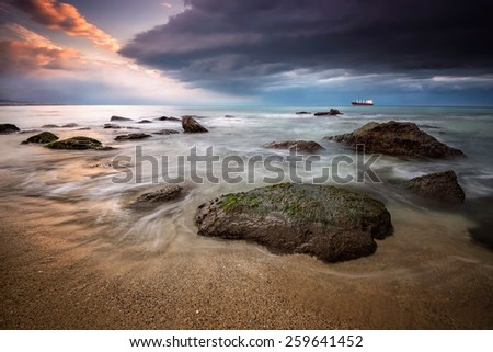 A stunning sunrise with stormy sea  - stock photo