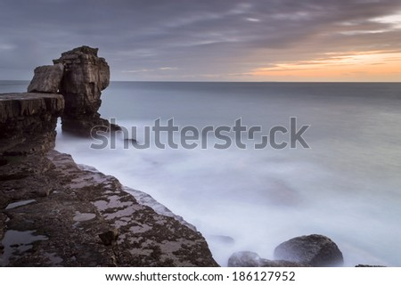 A stunning sunset at Pulpit rock on the Isle of Portland with the full force of the English Channel crashing against the rocks.