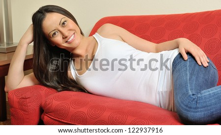 A stunning young biracial woman (Caucasian and Asian) rests on a Chaise Lounge wearing a white tank top and blue jeans, smiling. - stock photo