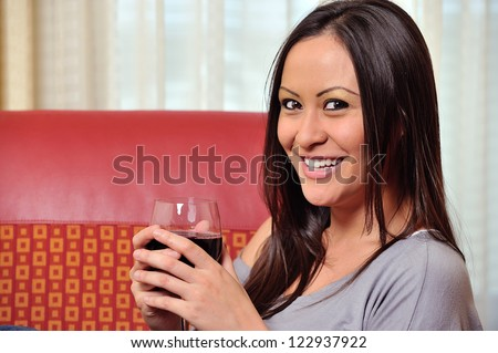 A stunning young biracial woman (Caucasian and Asian) smiles as she holds a glass of red wine. - stock photo