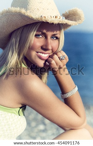A stunningly beautiful young blond woman enjoys the sunshine on a beach with blue sea in the distance